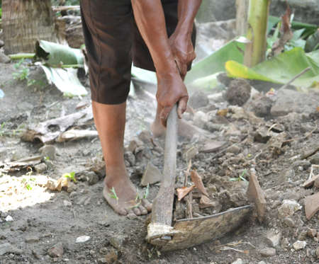 Old People Hands Use Hoe To Level The Ground And Dusty Stones In The Garden During The Day