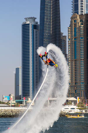 sportsman doing stunts on a background of the towers of Dubai Marina in the competition for the fly boarding at SkyDiveDubai in Dubai in 2014