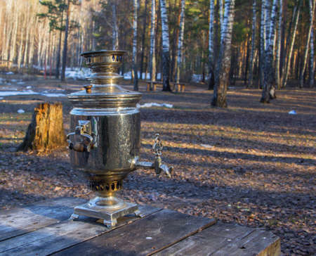 first spring tea from a samovar in the woods with melted snow photo