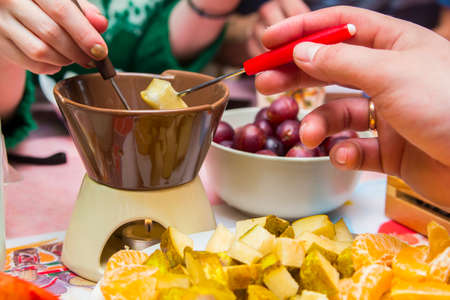 couple in love eating chocolate fondue with fruit on a romantic date photo