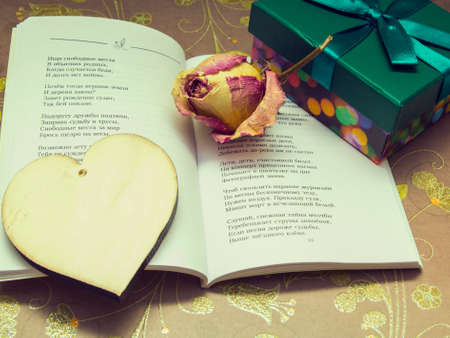 preparation for Valentines Day: a poem, a wooden heart, dried roses and a box with a gift