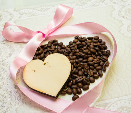 two hearts and a wooden coffee with a pink ribbon on a light background lace photo