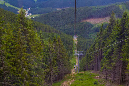 Cableway at Mount Snow in the Czech Republic, passing through the pine forest photo