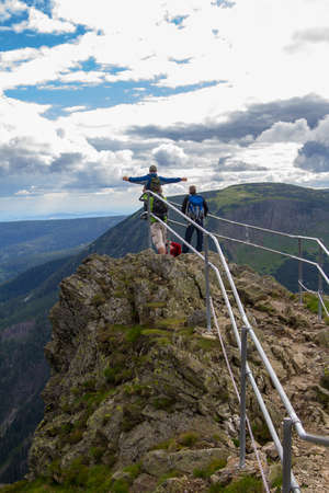 Three men on a mountain top over the precipice in the Czech Republic Stock Photo