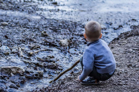 little boy playing in the creek in early spring photo