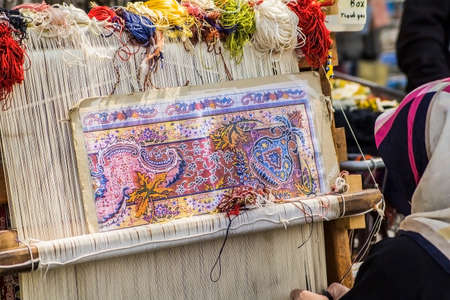 skilled weaver: Turkish carpet weaver weaves on a loom on the streets of Istanbul Stock Photo