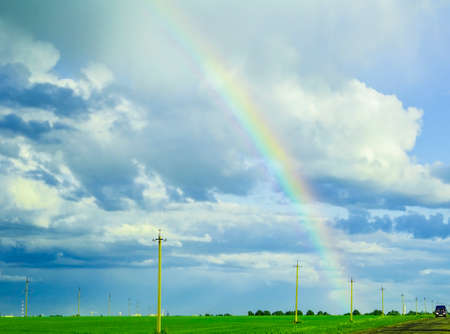 stormy sky: bright rainbow in the stormy sky over the green meadow Stock Photo