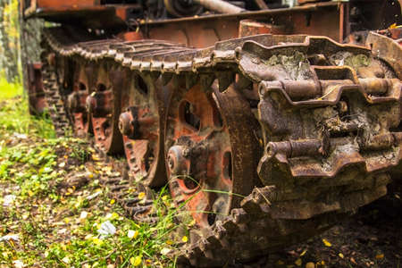 useless: background blur caterpillar old rusty tractor abandoned in the woods