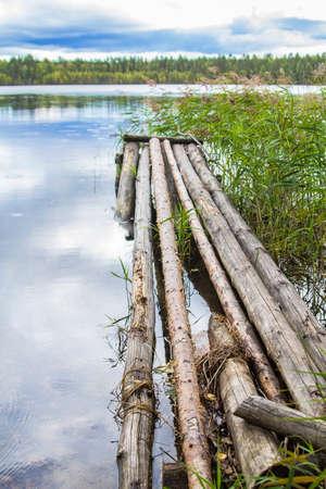 footbridges: background landscape forest lake under a cloudy sky with old wooden footbridges of logs