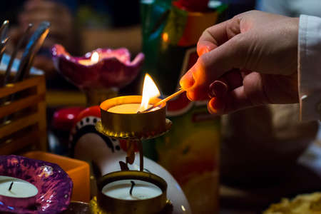 candle wick: background blurred womans hand lights a candle in a candlestick with a match at dusk