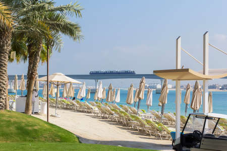 persian gulf: background landscape view of beach on the island of Palma with umbrellas and sunbeds, overlooking the Persian Gulf and the monorail Stock Photo