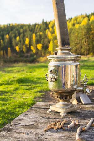 黄色い秋の森と川を背景に木製のテーブル背景風景サモワール光沢のある金属