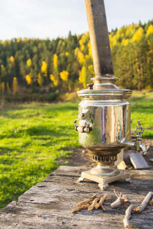 background landscape samovar shiny metal on a wooden table on a background of yellow autumn forest and river