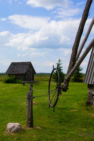 Background landscape view of an old mill, a barn and a field in the museum complex of ancient everyday life Dudutki, Minsk region, Belarus Stock Photo