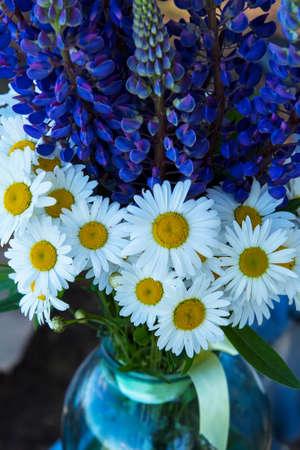 背景ぼやけて風景、ヒナギクとガラスの瓶にルピナスの花の夏の花束