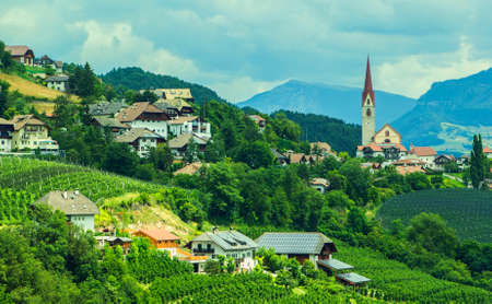Alpine village in the green valley among the mountains, In Italy Stock Photo