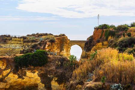 ラゴス、ポルトガルのアルブフェイラのビーチの一つの岩の間のアーチ型の橋の背景風景を見る 写真素材