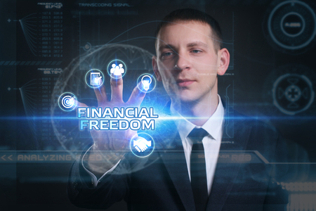 financial freedom: Business, Technology, Internet and network concept. Young businessman working on a virtual screen of the future and sees the inscription: financial freedom Stock Photo
