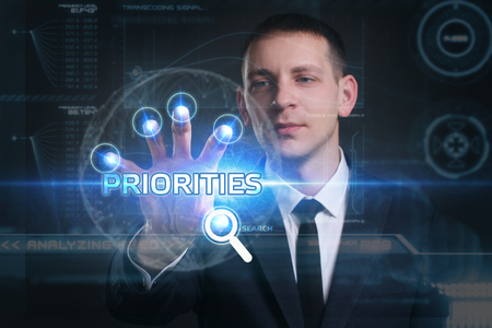 virtual technology: Business, Technology, Internet and network concept. Young businessman working on a virtual screen of the future and sees the inscription: priorities