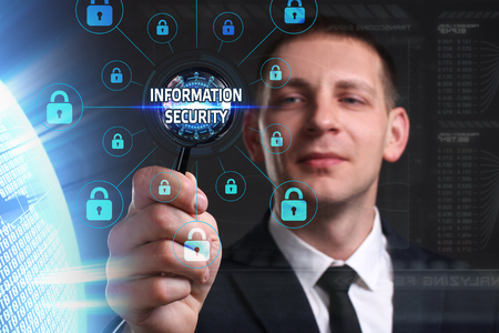 background information: Business, Technology, Internet and network concept. Young businessman working on a virtual screen of the future and sees the inscription: Information security
