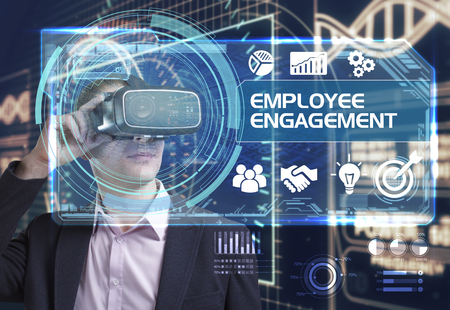 Business, Technology, Internet and network concept. Young businessman working in virtual reality glasses sees the inscription: employee engagement