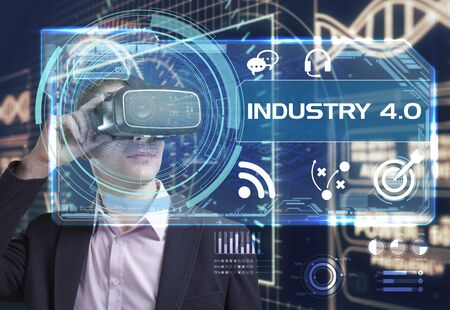 Business, Technology, Internet and network concept. Young businessman working in virtual reality glasses sees the inscription: industry 4.0