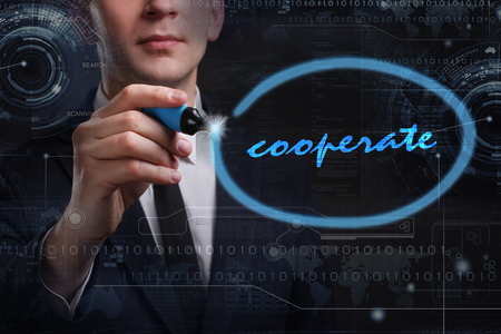 cooperate: Business, Technology, Internet and network concept. Young business man writing word: cooperate