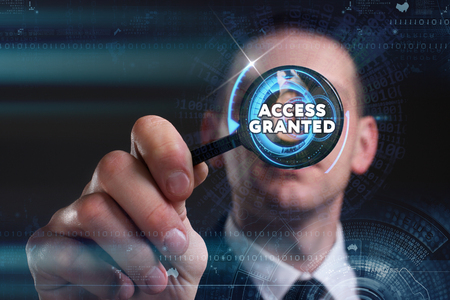 granted: Business, Technology, Internet and network concept. Young businessman working on a virtual screen of the future and sees the inscription: access granted
