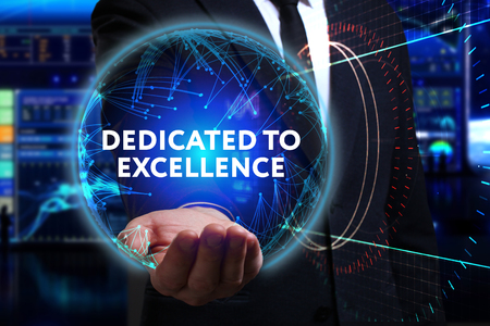 Business, Technology, Internet and network concept. Young businessman working in the field of the future, he sees the inscription: dedicated to excellence Stock Photo