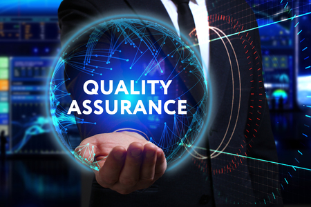 Business, Technology, Internet and network concept. Young businessman working in the field of the future, he sees the inscription: quality assurance