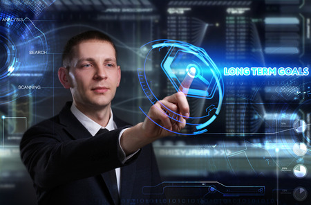 long term: Business, Technology, Internet and network concept. Young businessman working on a virtual blackboard of the future, he sees the inscription: long term goals