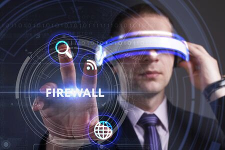 Business, Technology, Internet and network concept. Young businessman working in virtual reality glasses sees the inscription: Firewall Stock Photo