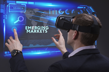 emerging economy: Business, Technology, Internet and network concept. Young businessman working on a virtual screen of the future and sees the inscription: Emerging markets