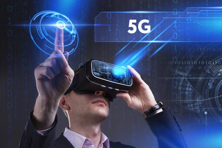 ビジネス、技術、インターネット、ネットワークのコンセプトです。仮想現実の眼鏡で働く青年実業家は、碑文を見ている: 5 G 写真素材