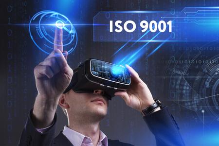 ビジネス、技術、インターネット、ネットワークのコンセプトです。仮想現実の眼鏡で働く青年実業家が碑文を見る: ISO 9001