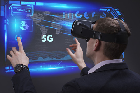 Business, Technology, Internet and network concept. Young businessman working on a virtual screen of the future and sees the inscription: 5G Banco de Imagens