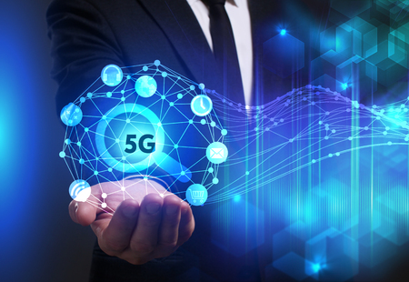 Business, Technology, Internet and network concept. Young businessman working on a virtual screen of the future and sees the inscription: 5G Фото со стока