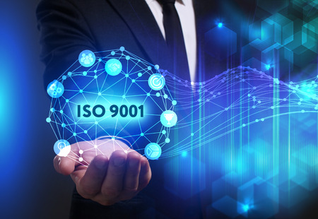 Business, Technology, Internet and network concept. Young businessman working on a virtual screen of the future and sees the inscription: ISO 9001
