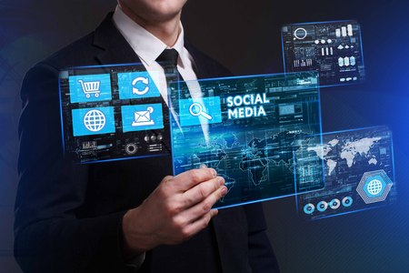 media gadget: Business, Technology, Internet and network concept. Young businessman working on a virtual screen of the future and sees the inscription: Social media Stock Photo