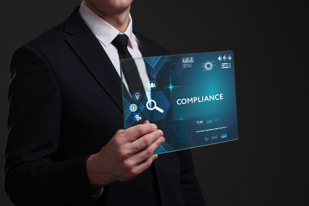 keyword: Business, Technology, Internet and network concept. Young businessman working on a virtual screen of the future and sees the inscription: Compliance