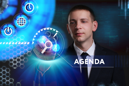 keyword: Business, Technology, Internet and network concept. Young businessman working on a virtual screen of the future and sees the inscription: Agenda
