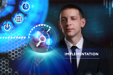 keyword: Business, Technology, Internet and network concept. Young businessman working on a virtual screen of the future and sees the inscription: Implementation