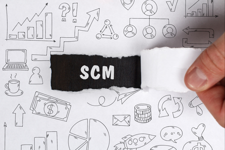 scm: Business, Technology, Internet and network concept. Young businessman shows the word: SCM