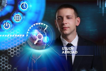 keywords link: Business, Technology, Internet and network concept. Young businessman working on a virtual screen of the future and sees the inscription: Study abroad
