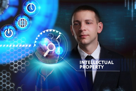 keywords link: Business, Technology, Internet and network concept. Young businessman working on a virtual screen of the future and sees the inscription: Intellectual property