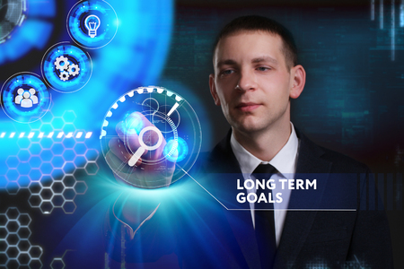 Business, Technology, Internet and network concept. Young businessman working on a virtual screen of the future and sees the inscription: Long term goals