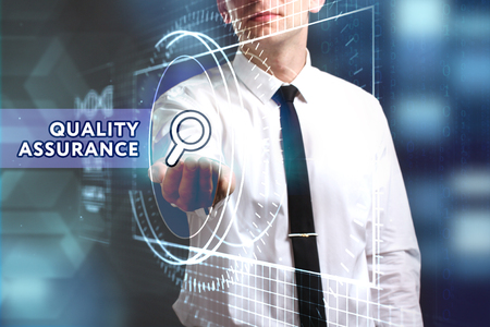 keywords link: Business, Technology, Internet and network concept. Young businessman working on a virtual screen of the future and sees the inscription: Quality assurance Stock Photo