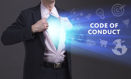 keywords link: Business, Technology, Internet and network concept. Young businessman shows the word: Code of conduct