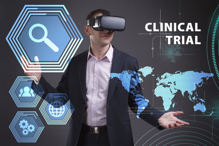 keywords link: Business, Technology, Internet and network concept. Young businessman working on a virtual screen of the future and sees the inscription: Clinical trial Stock Photo
