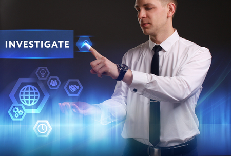 keywords link: Business, Technology, Internet and network concept. Young businessman working on a virtual screen of the future and sees the inscription: Investigate Stock Photo